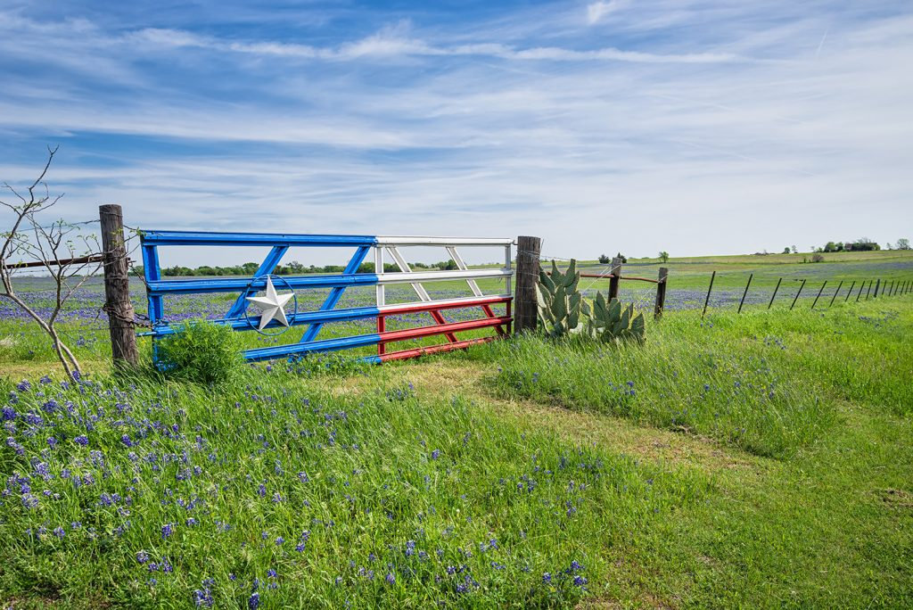 Texas landscape with a fence with a Texas flag gate